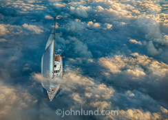 An aerial view of a yacht shows the sailboat cutting through mist and fog in a stock photo about navigation, risk and challenge as well as skill and daring.