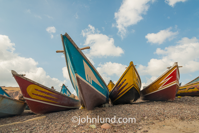 Yemeni (Socotran) fishing boats line the beach in dramatic fashion against a clear blue sky in this travel photograph.