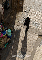 A Yemeni woman wears her Abaya as she walks through a market in Saana, Yemen.