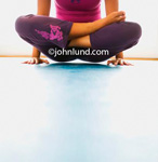 Photo of a woman in a lotus position but holding herself up with her arms so her butt doesn't touch the ground. A hard yoga positon to maintain. Yoga pics.