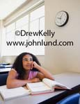 Picture of an African American student daydreaming when she should be studying. The girl has long black hair and is wearing a pink blouse.  Pictures of  high school students in class rooms. The female student is resting her cheek on her hand.