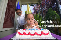 Picture of a young ethnic girl wearing a party hat and blowing the candles out on her birthday cake. Behind the girl is a little boy also wearing a birthday party hat. Kids at birthday parties.