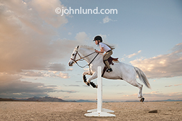 A young girl guides her horse over a jump in a stock photo about determination, courage and achievement as well as equestrian issues.