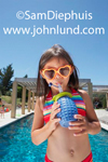 A cute young girl in a bikini swim suit is standing in front of a swimming pool, looking at the camera as she drinks from a plastic water bottle and wears heart-shaped orange colored sun glasses.