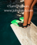 A picture from mid-thigh down from behind of a pair of legs with swim flippers on the feet. Young girls legs with swim fins on her feet as she stands on a diving board at a swimming pool.