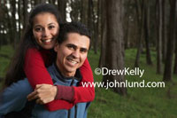 A happy smiling couple hugging in the deep woods of the forest. Stock image of a happy hispanic couple in the forest. The man is giving the woman a piggy back ride in the woods.