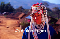 Picture of a young Burmese tribal woman with an elaborate head dress and costume. She wears the traditional clothing of her Hmong tribe in Burma (Myanmar).