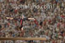 A young female gymnast performs a somersault or back flip on the balance beam in a gymnastic competition before a huge crowd.