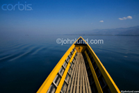Picture of a yellow boat on a calm and serene lake, Inle lake in Myanmar.