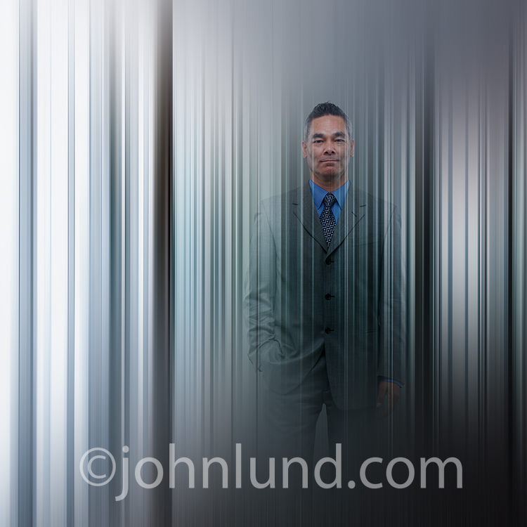 A businessman materializes in a futuristic scene of vertical lines in an image about future technology in business including holograms, cloud computing, and even artificial intelligence.