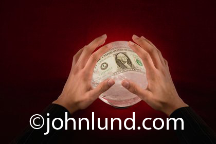 Photo of a pair of hands hovering over an internally illuminated crystal ball with a one dollar bill visible in the ball. A fortune teller's hands over  a crystal ball with money showing inside.