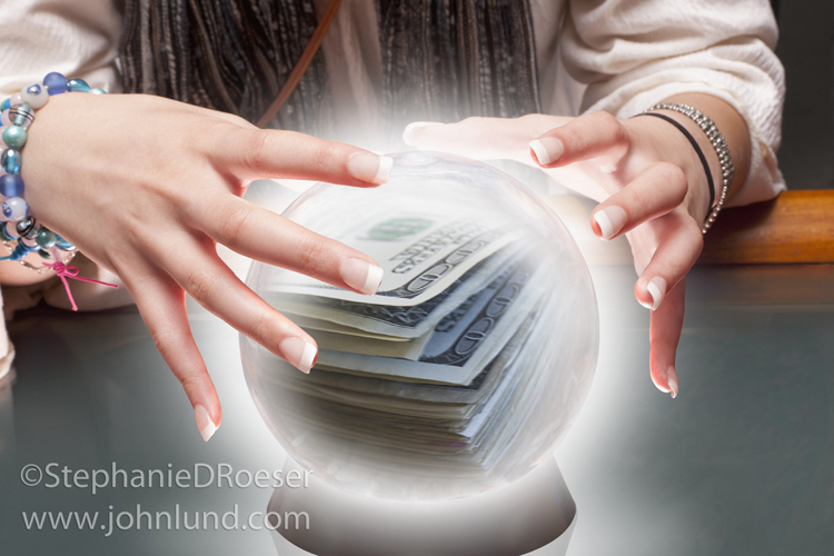 A fortune teller's hands, a crystal ball, and money are the key elements in this stock photo about future financial success.
