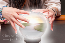 A pathway to the future is revealed in a crystal ball in this photo of a Gypsy fortune teller's hands above her magic orb.