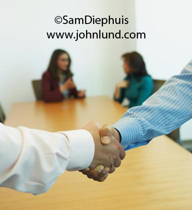 Close up picture of a business handshake. Two hands shaking closeup to close a business deal in the boadroom with the conference table and other executives in the background. Business handshake pics for advertising.