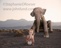 A baby in diapers sits in front of a huge elephant and mimics him using a paper towel cardboard insert in this humorous stock photo.