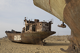 Stranded Ships lay strewed across the sand left behind the disappearing waters of the Aral Sea in a travel and stock photo.
