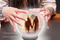 Picture of a fortune teller's hands over a crystal ball with a couple holding hands inside in an image about finding love.
