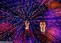 A businessman holds up a phone with streaks of colored light representing data flowing towards or away from the phone