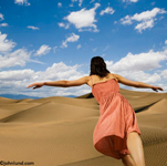 A woman, arms outstretched, runs in freedom across desert sands in this concept stock photo. The sand dunes reach off into the horizon and the sky is blue with a few fluffy clouds. The woman has an orange dress on.