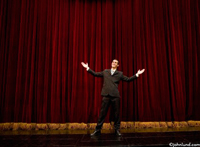 Picture of a businessman on stage giving a presentation. The man has his arms spread out in a gesture of welcome.  The gentleman is wearing a dark business suit, and the theater curtains are maroon.