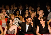 A rude man is using his cell phone in a crowded theater much to the ire and irritation of the surrounding members of the audience. People nearby are glaring and staring at him with anger and irritation.