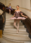 Pictures of two ballerinas on a staircase wearing TuTus as they prepare to visit with admiring fans. The young women are gracefully descending the staircase as one would expect ballerinas to do.