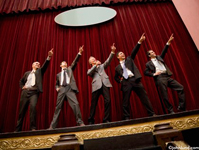 Picture of businessmen performing a song and dance routine on stage in a parody of business presentations. A chorus line of businessmen performing on stage. The men are dancing.