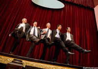 Pictures of men dancing the can can on stage in business suits. The background is a dark maroon stage curtain. The men are wearing business suits and their arms are interlocked.