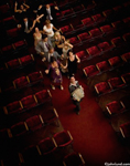 Pictures of a pied piper in a theater showing leadership and playing a musical instrument. A large group of people are following him down the aisle.