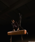 Man on pommel horse wearing a business suit as he performs his gymnastics routine require skill, focus and dedication.