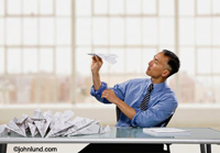 An Asian American businessman sits at his desk folding paper airplanes in a parody of mass mailings and communication. The man is in the act of launching his paper aircraft.  Paper airplane pic.