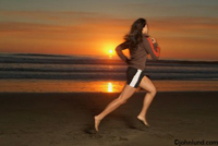 An Asian woman runs on the beach as the sun sets over the Pacific Ocean. Beautiful scenic orange sunset with the bright orange globe dropping below the horizon. Fit woman running on the beach at San Francisco, California.