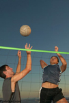 Photos of two volleyball players; one is setting the ball up while the other prepares to spike the ball. Men playing beach volleyball at sunset.