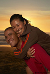 An African American man gives a piggy back ride to an Asian woman as they enjoy the sunset at the beach. A happy interracial couple in love and enjoying a beautiful sunset.