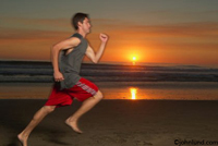 Photos of a man running on a sandy beach just as the sun sets over the Pacific ocean. Beautiful orange sunset with the sun just about to dip below the horizon.