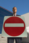 Photo of a business man holding up a dead-end road sign. The man is a black man and the sign is red and white, a traditional dead end sign for streets, roads, and highways.