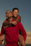 Photos of a man giving a woman a piggy back ride at sunset on the beach. The pair are happy and smiling and having loads of fun.