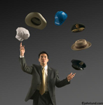 Man juggling a number of hats including a chef's hat, a cowboy hat, hard hat, police cap and more. A man of many hats.