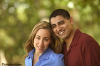 Photos of a happy and affectionate upscale hispanic couple shot outdoors with out of focus trees providing a pleasing background.