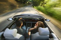 Photos of a couple in a convertible driving down a tree lined road. Picture taken from the rear looking forward.