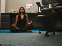 A woman sits on her cubicle floor and does Yoga poses. The woman appears to be in the classic lotus position.  Office chairs and desks surround her.