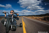 Photos of a young boy emulating a motorcycle rider while sitting on a tricycle. You can tell he thinks he is a Bad Boy! The youngster riding the trike is Mexican, Latino, or Hispanic.