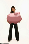 East Indian woman with a giant piggy bank in her arms in a picture about personal finance and savings. The pretty and attractive young Indian woman has long dark hair and is smiling as she holds the piggybank with both hands.