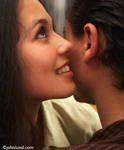 Lifestyle photo of an Hispanic woman whispering in a man's ear. Very attractive, beautiful, Latina woman cheek to cheek with the man she is whispering too.