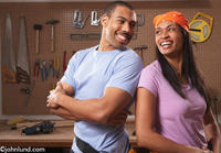 A man and woman stand together in their garage before starting a home improvement project. This African American couple enjoy DIYS projects! Behind the couple on the wall is a classic pegboard with tools of all sorts hanging from the pegs.