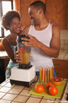 Lifestyle photo of an African American couple making breakfast together in their kitchen. They are happy and smiling and he is using a food processor to make orange juice drinks.