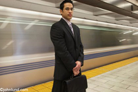 A business man stands with his briefcase in the subway as a train speeds by in the backgrouond
