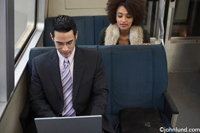 Two business people of ethnic descent sit on a commuter train and work on thier laptops. A man and a woman are both working on their laptops while riding the subway.