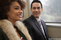 An African American Woman and a Chinese American man are seated together on a commuter train.The man and woman are smiling and happy chatting on their way to work.