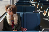 A woman sits alone on a train and gazes out the window as she is lost in thought